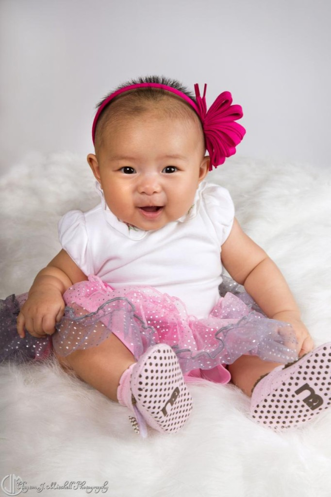 smiling baby in pink and white