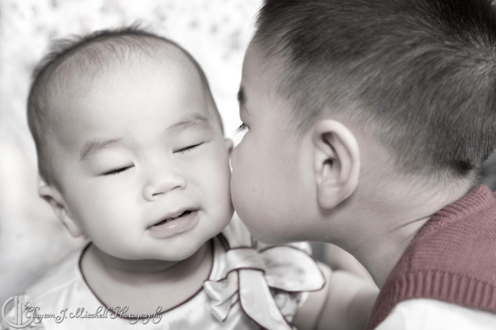 brother kissing baby sister