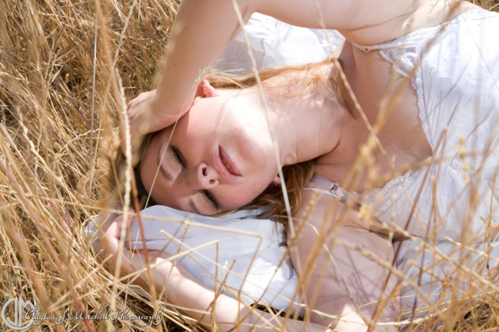 blonde woman laying in grass