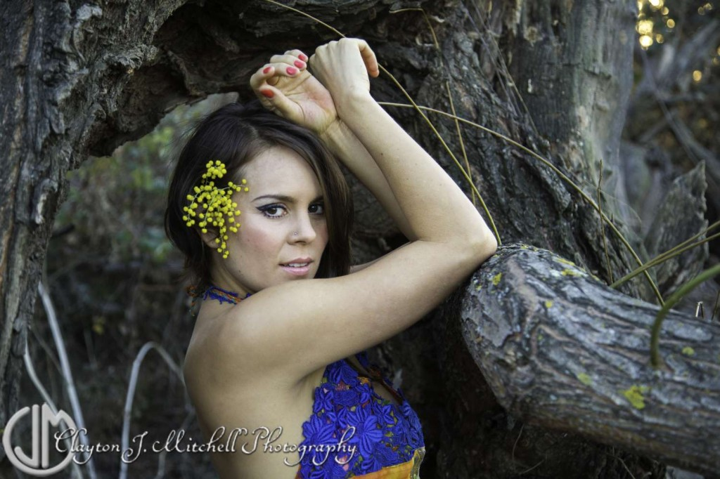 Woman posed with tree branch and yellow flowers