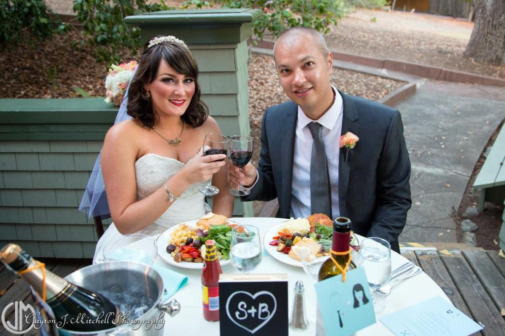 bride and groom eating dinner at sweetheart table