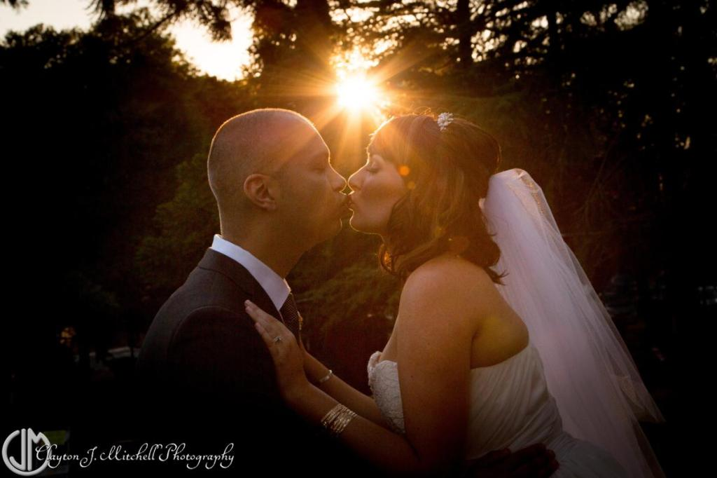 bride and groom kissing and sunflare romantic wedding photography