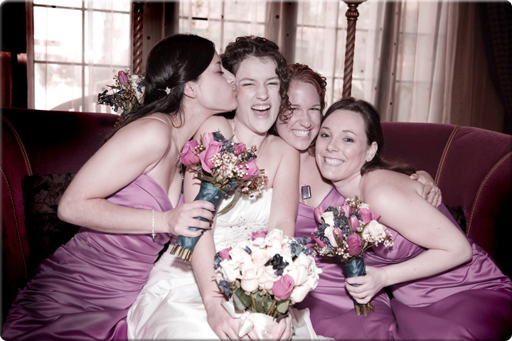 Bride being kissed by bridesmaid